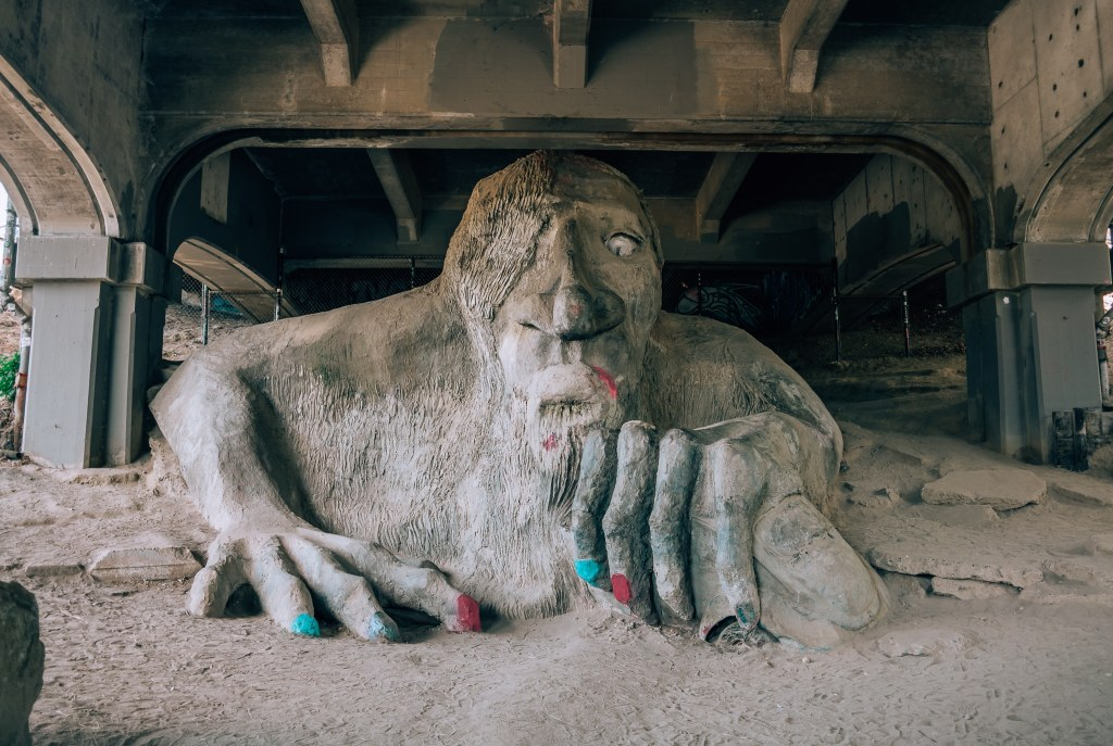 Art installation of a troll underneath the Fremont Bridge in Seattle with its nails painted red and blue