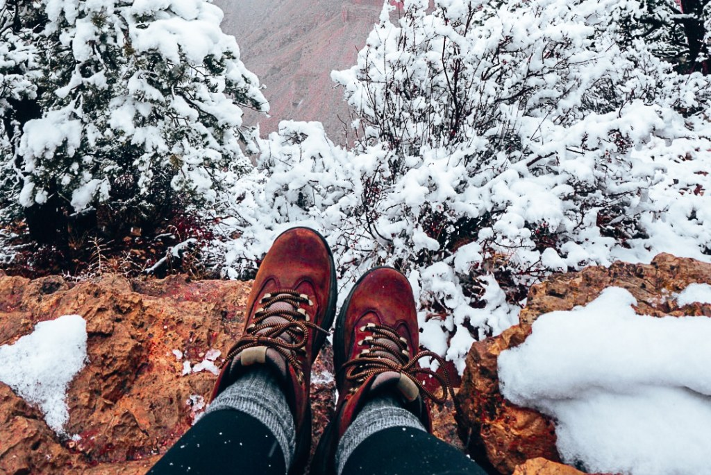 Hiking boots sitting along the edge of the Grand Canyon in winter, both covered in snow.