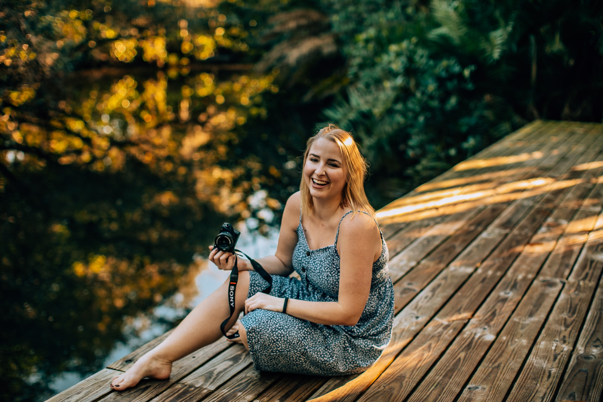 Woman sitting on a wooden platform over a swamp at Koreshan State Park in Naples, Florida. She is smiling and holding a camera.