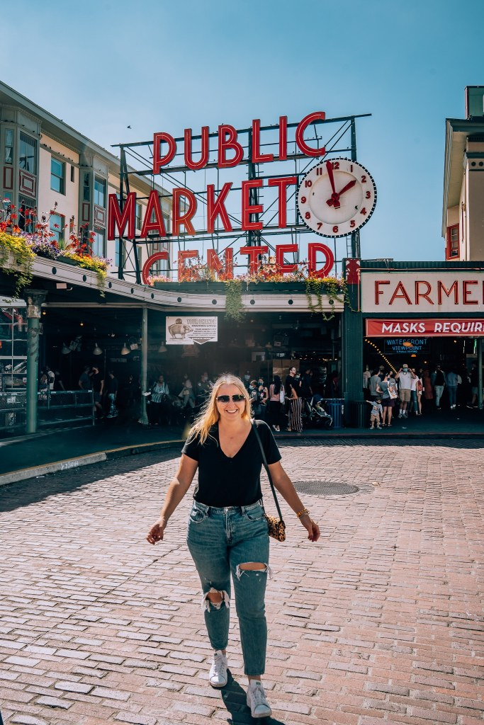 Woman walking in front of the iconic Pike's Place Market sign in Seattle, Washington