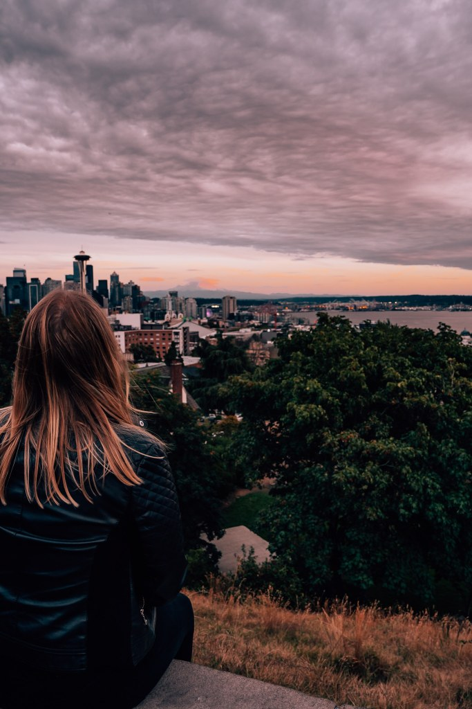 Woman sitting at Kerry Park during sunset, looking out at the Seattle skyline and Mount Rainier