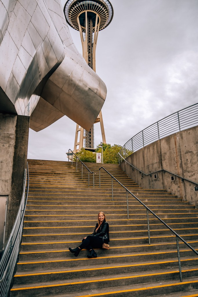 Woman sitting on some stairs in front of the Modern Pop Culture Museum and the Space Needle in Seattle
