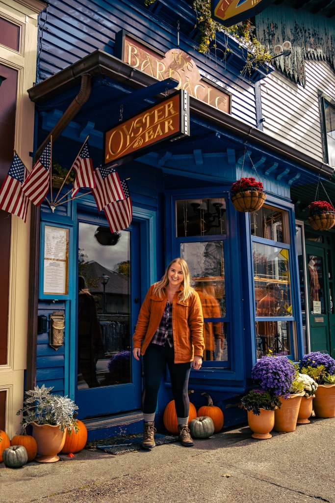 Woman standing in front of a blue building with pumpkins in front of it