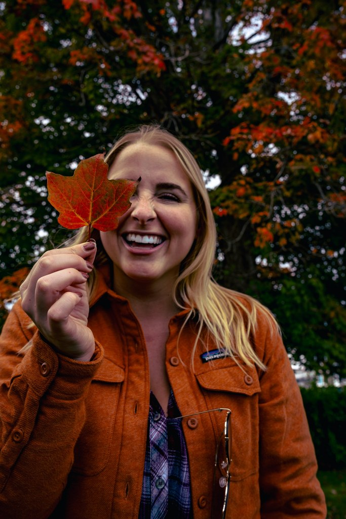 Smiling woman holding a red leaf in front of her face