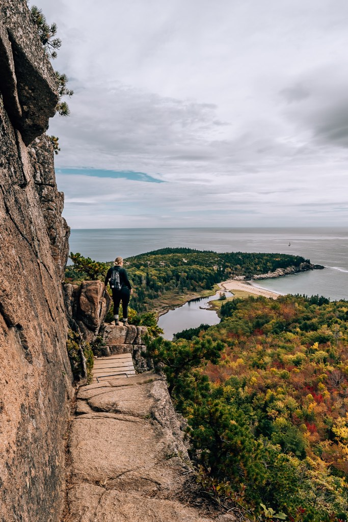 Woman standing along a cliff looking out to a view of fall trees and the Maine coastline