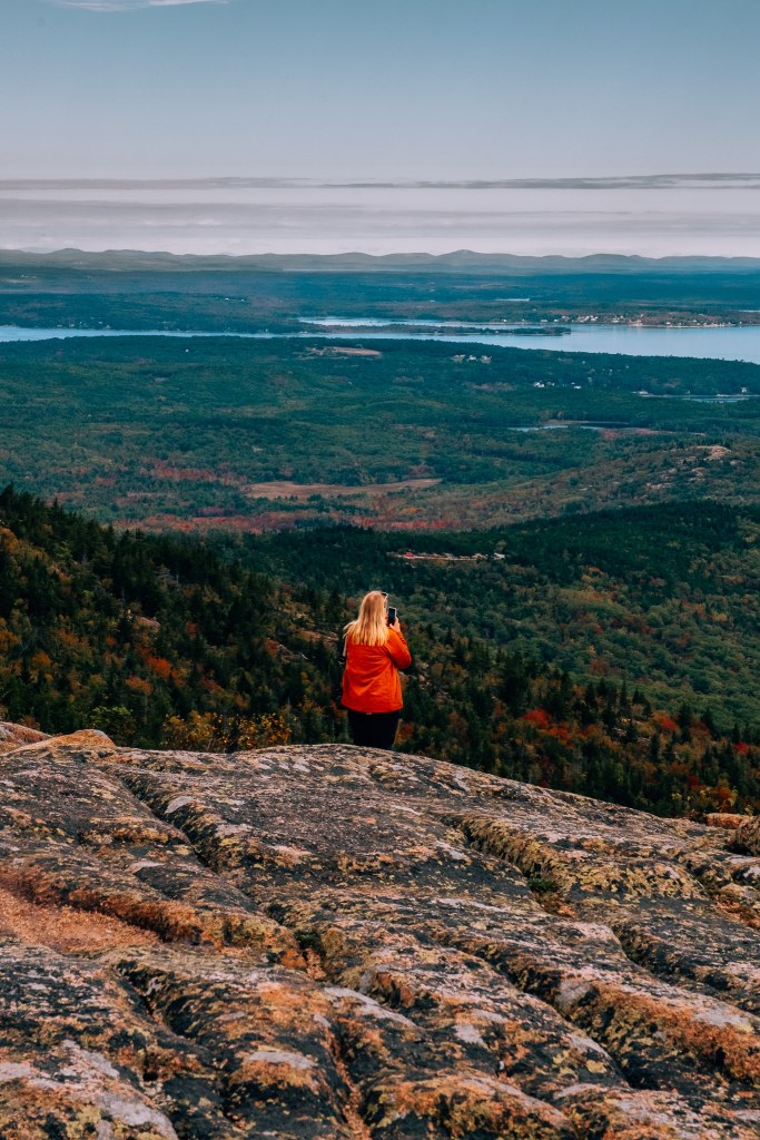 Woman standing atop a mountain looking out to the view with the coastline and many red and yellow trees for autumn