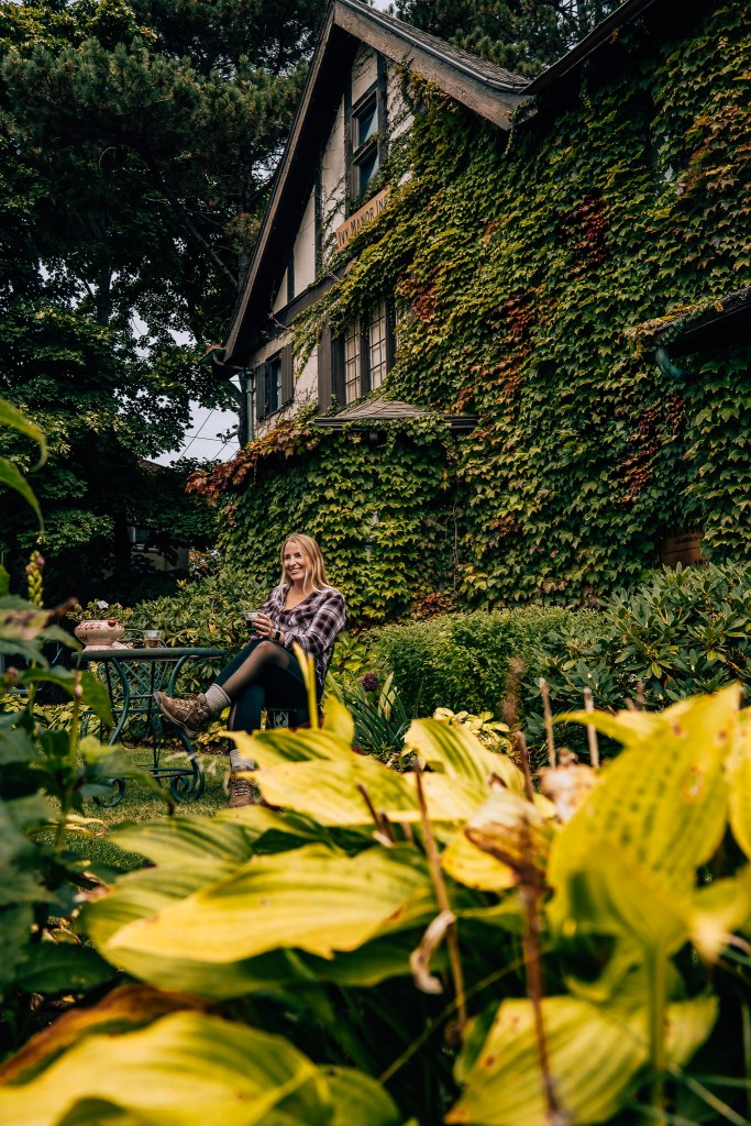 Woman sitting in front of an ivy-covered building drinking wine