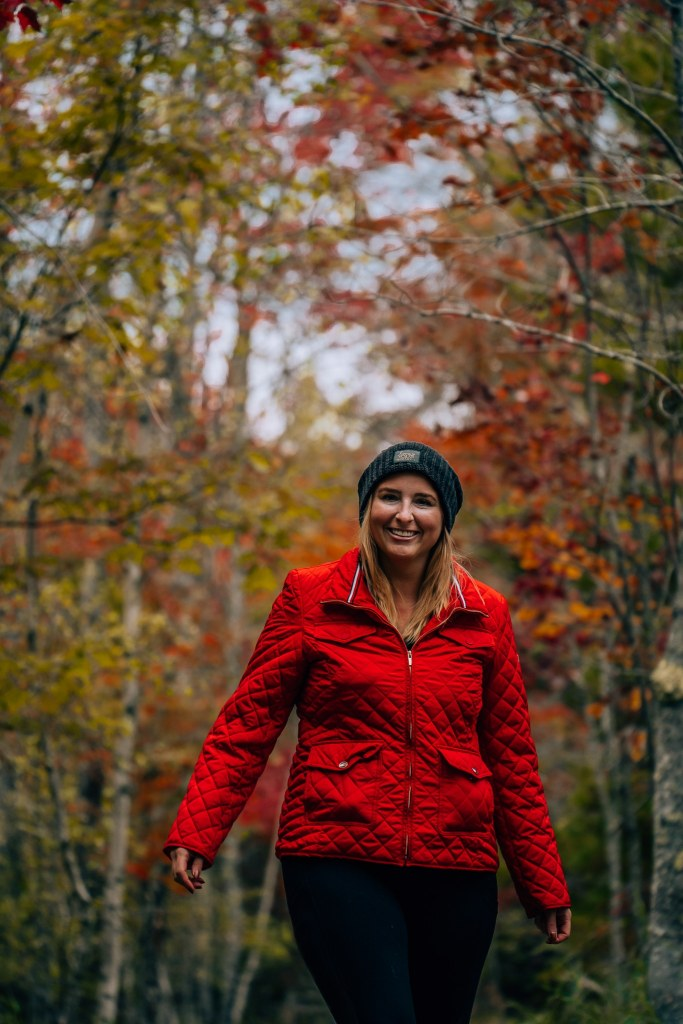 Woman in a red jacket standing amid brightly colored trees changing their leaves for fall