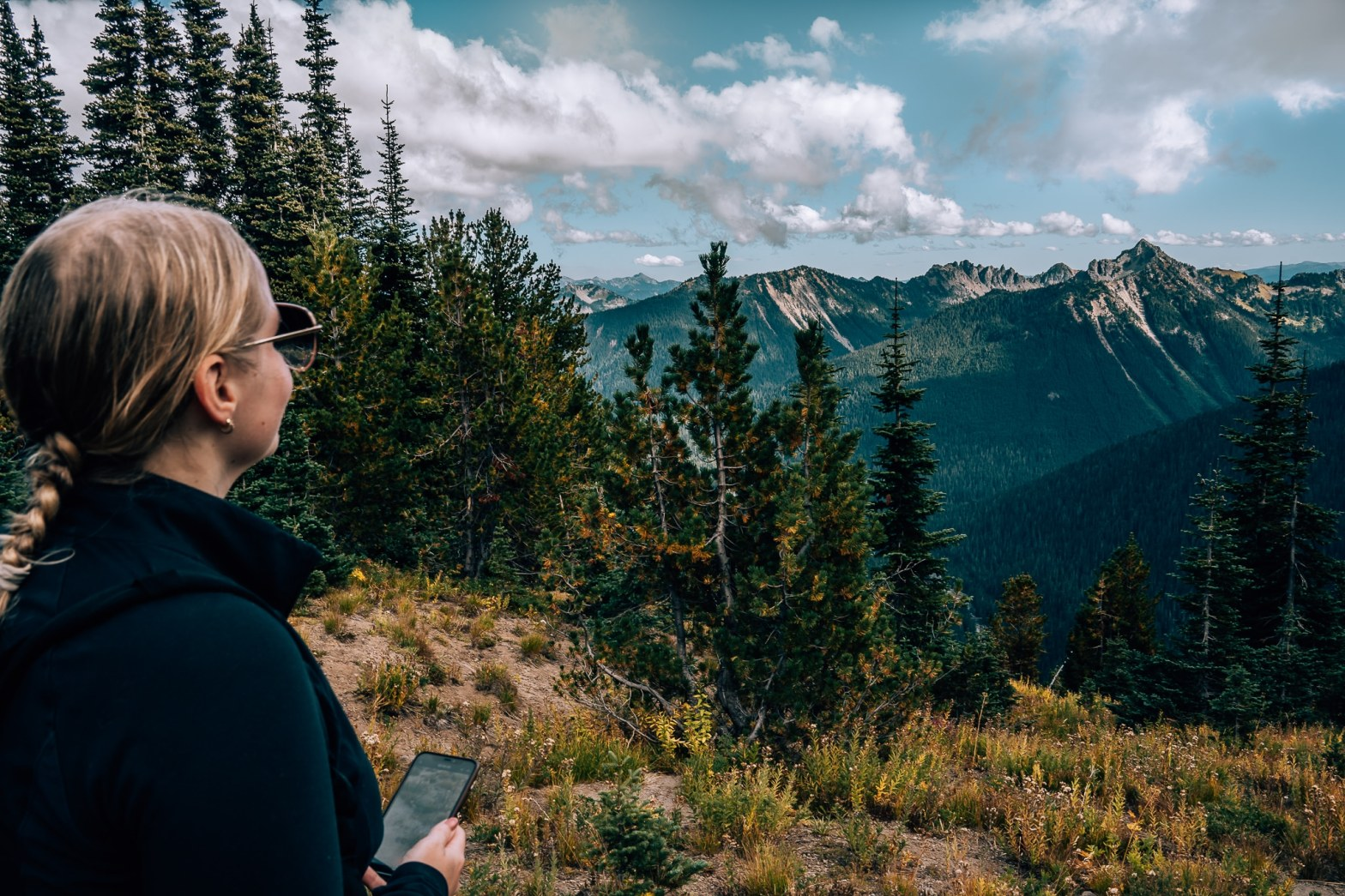 Woman holding phone, looking out to the mountains at Mount Rainier National Park