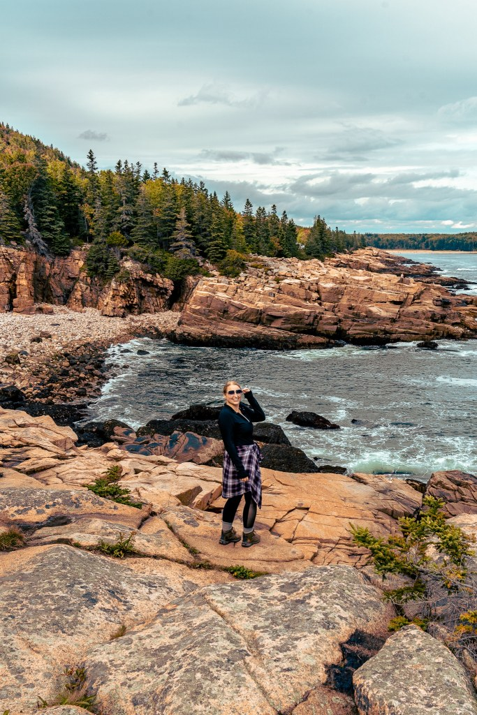 Woman standing at Schooner Head Overlook at Acadia National Park, with the coastline jagged behind her